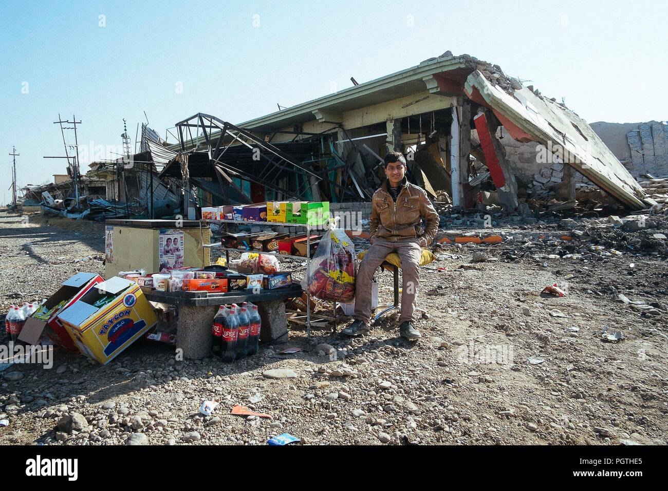 A sell food and drinks in front the ruin of a building in Qaraqosh the christian city destroyed by ISIS - Stock Image