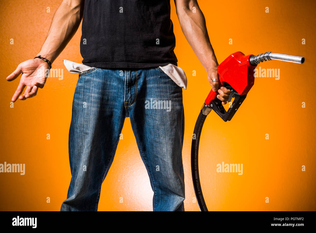 Empty pockets and gasoline pump nozzle. Concept is out of money for gas or gas is too expensive. - Stock Image