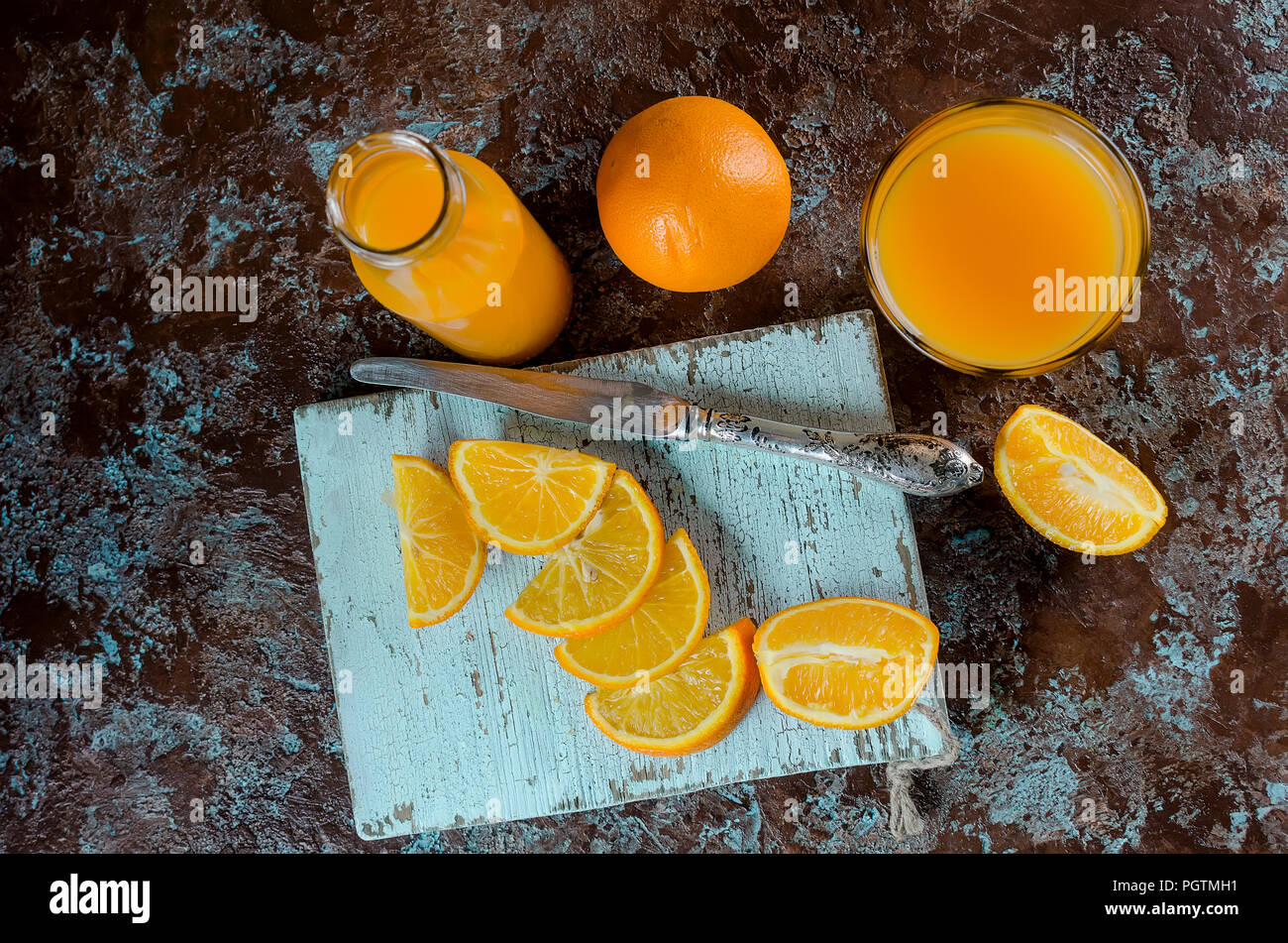 orange juice in a glass and a bottle and pieces of orange on a concrete brown-blue background copy space Stock Photo