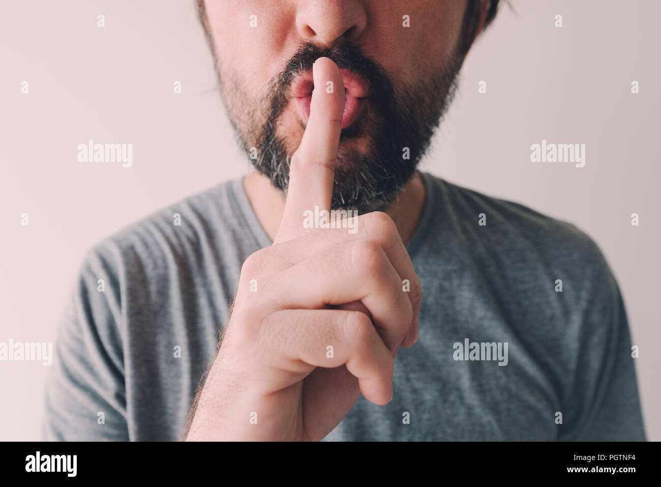 Finger on lips, man making a shushing gesture - Stock Image