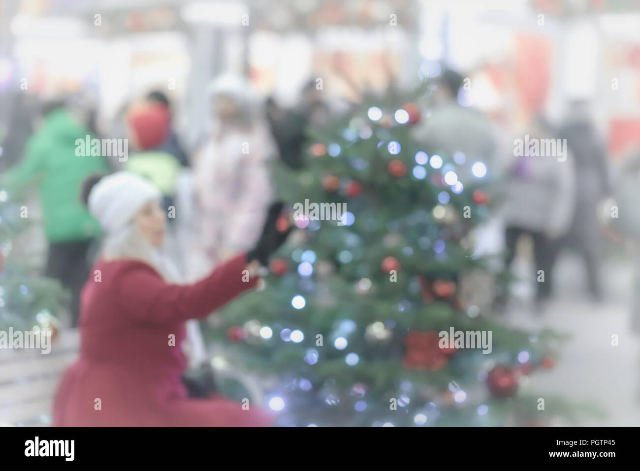 An unrecognizable girl in a red coat examines decorations on a Christmas decorated Christmas tree. Festive shopping and sales. Blurred Background - Stock Image