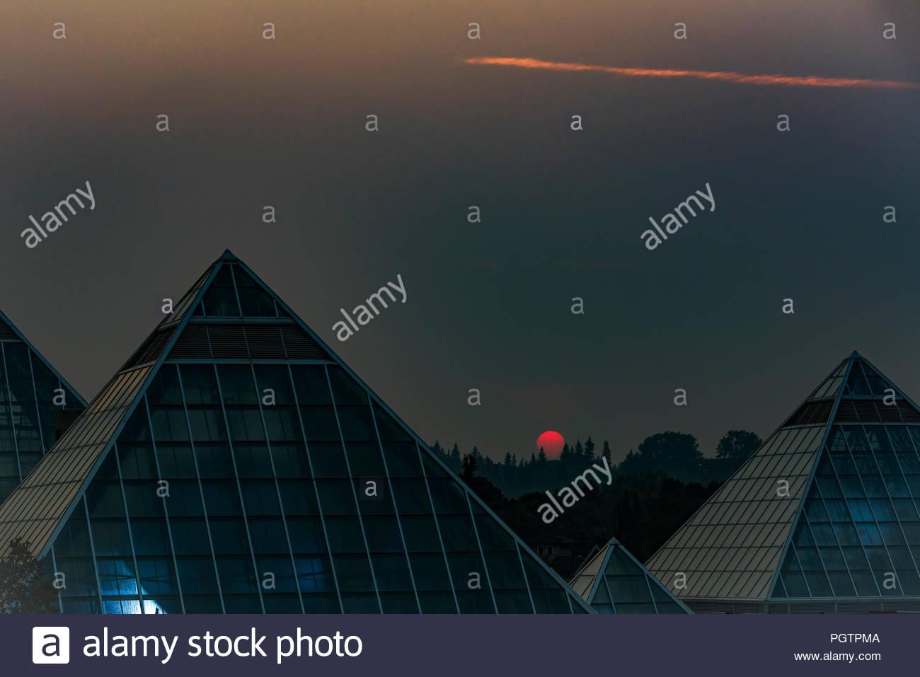 Sun rises through smoke filled sky, Muttart Conservatory Pyramids, Edmonton, Alberta, Canada. - Stock Image
