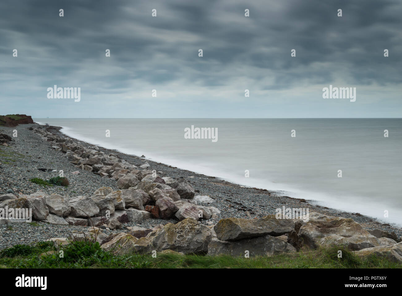 The deserted western shoreline and beach of Walney Island off the Cumbrian coast in summer with long exposure on the sea and shingle beach. - Stock Image