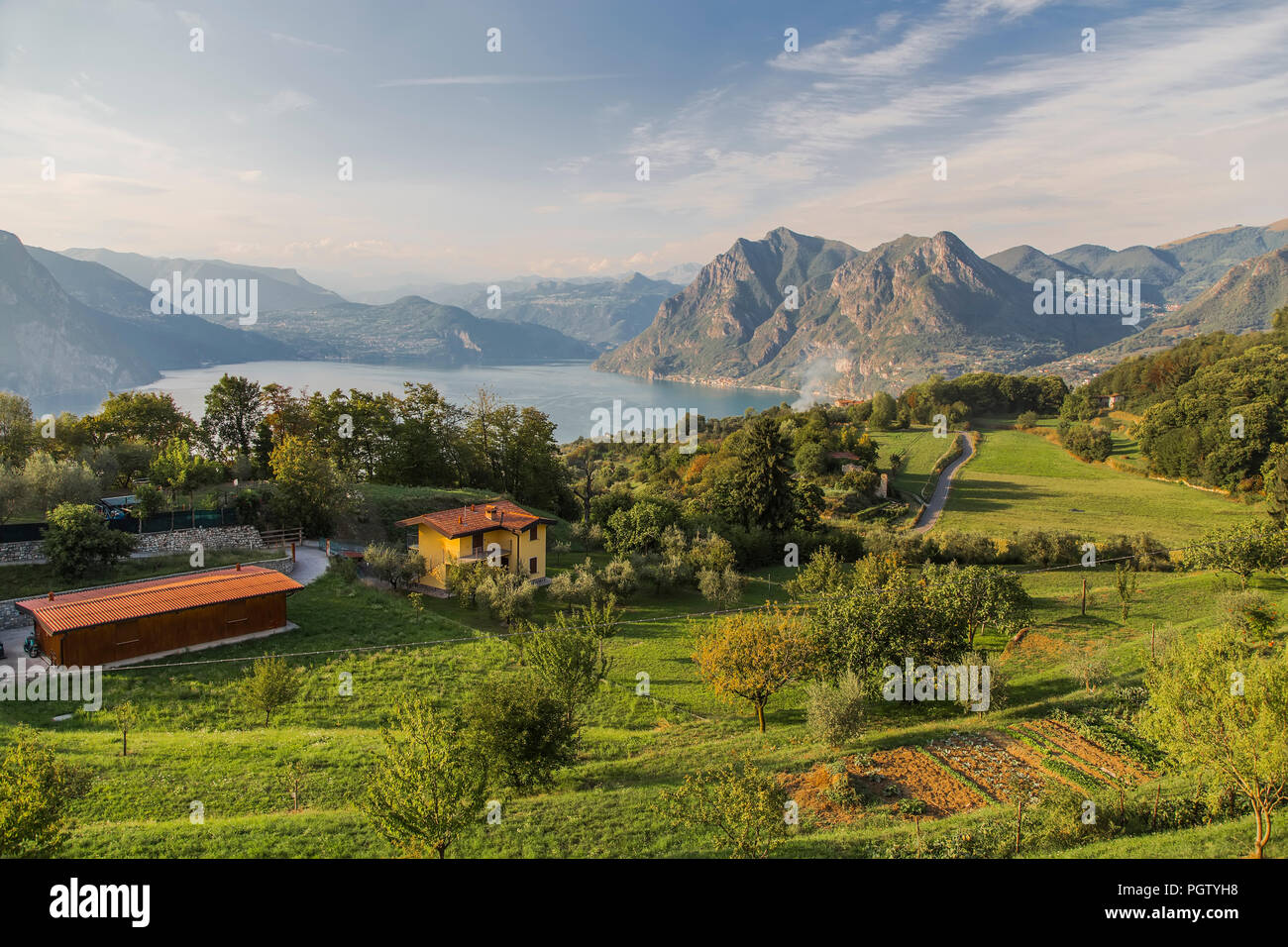 Rural house with fruit trees, vineyards and fields on the island in the middle of Lake Iseo and the mountains on the horizon. Italy - Stock Image