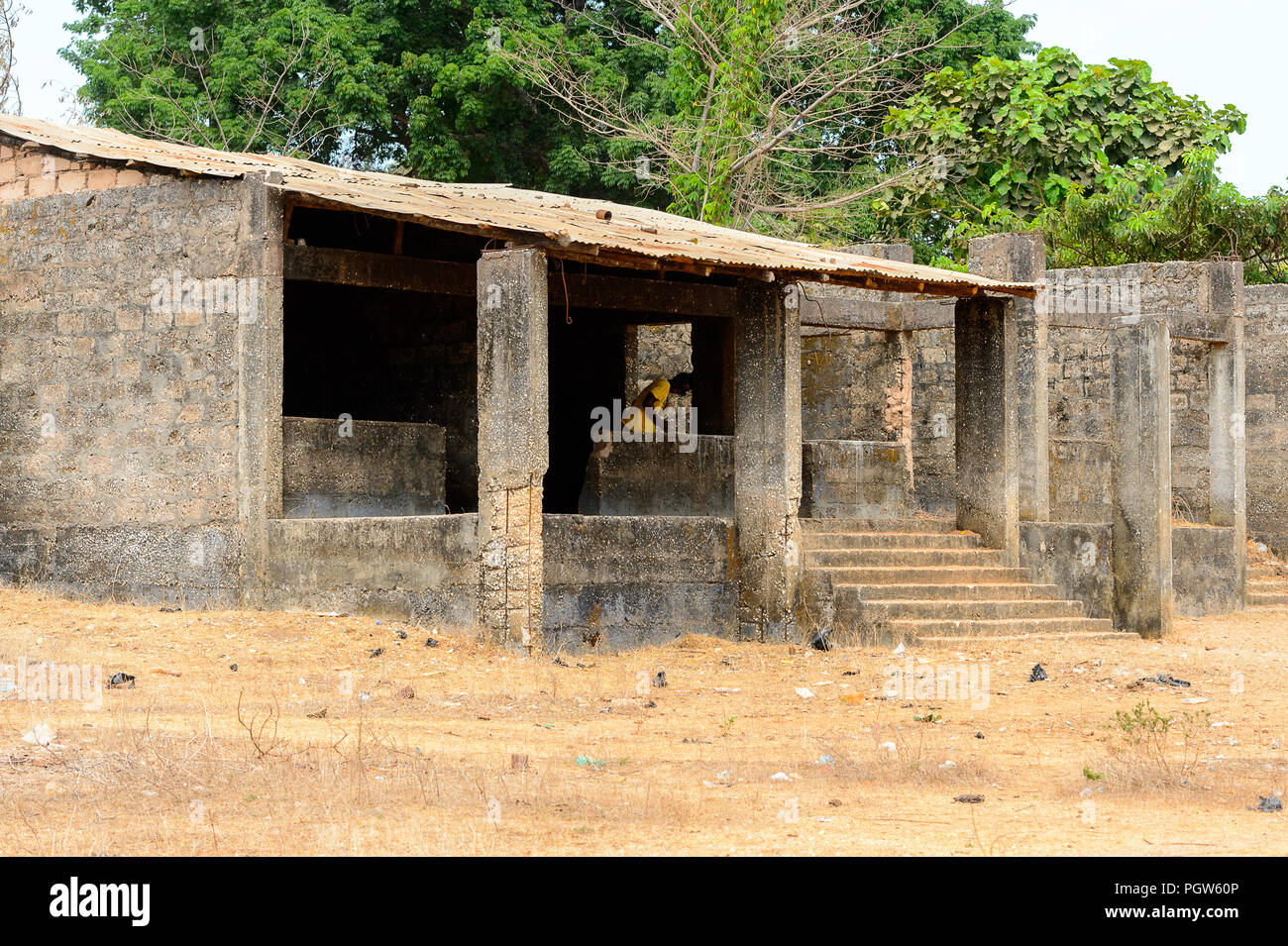 BUBAQUE, GUINEA BISSAU - MAY 5, 2017: Unidentified local man in yellow shirt stands in the unbuilt building in a village of the Bubaque island. People Stock Photo