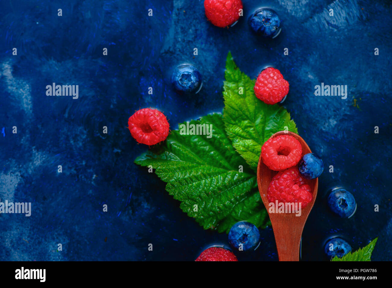 Summer berries in wooden spoons top view. Raspberry and blueberry mix on a dark blue wet background with copy space. Raw ingredients from above - Stock Image