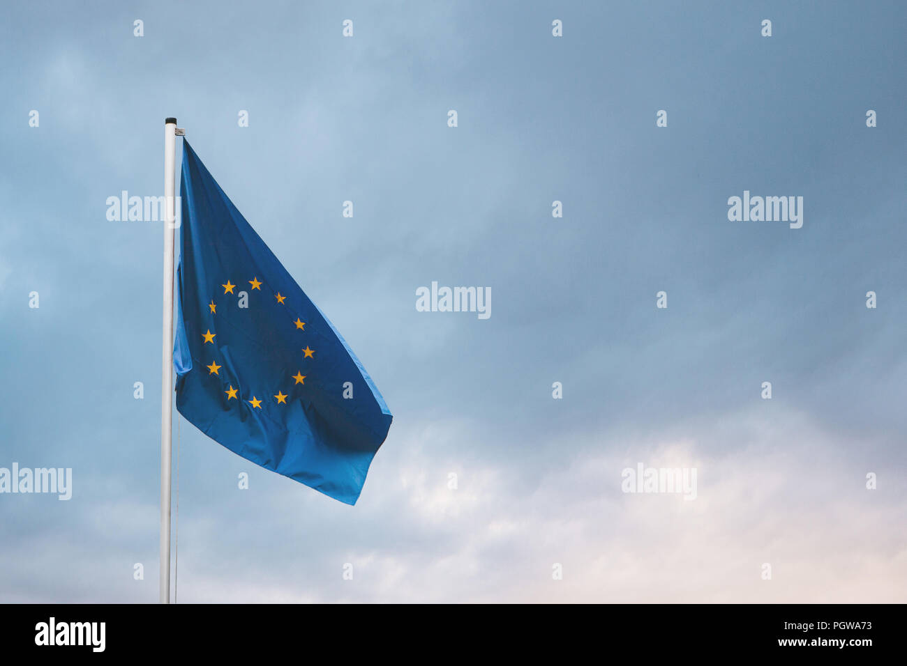 Flag of the European Union on the flagpole against the backdrop of the dramatic sky. - Stock Image