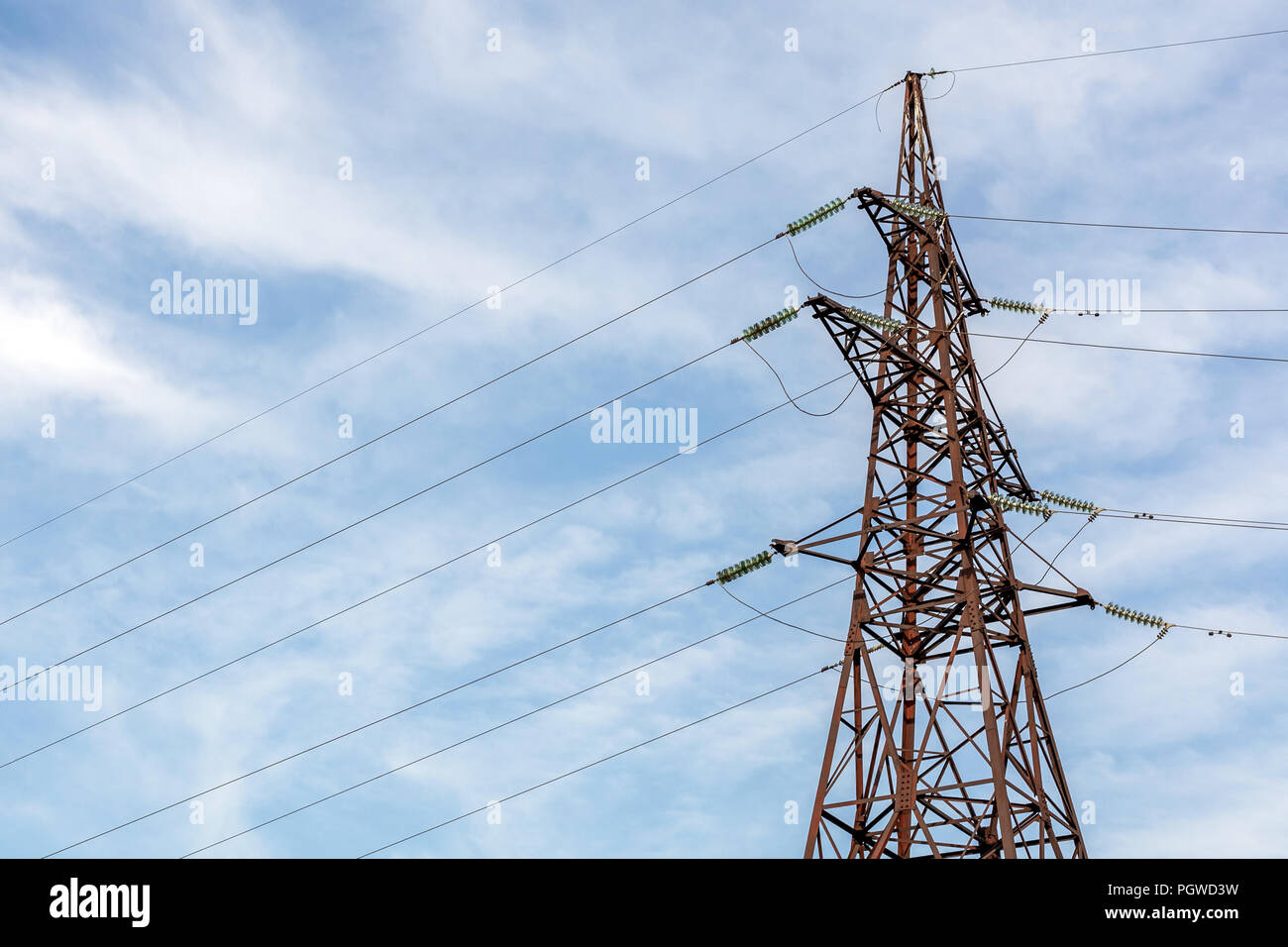 High-voltage electricity pylon with blue clear sky on background. Energy transmission. - Stock Image