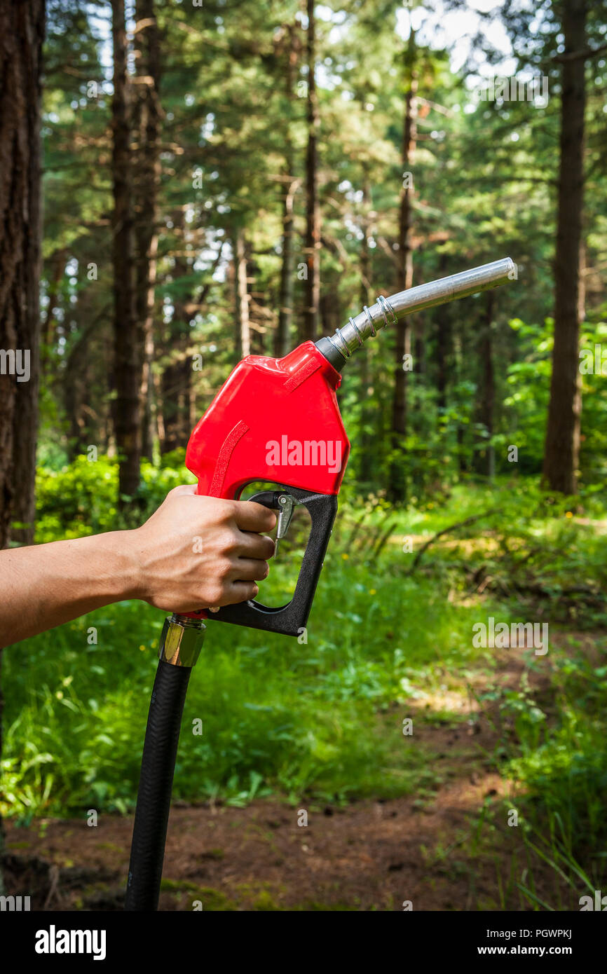 A human hand holding a gasoline pump nozzle in a forest setting. Concept, environmental issues around petroleum. - Stock Image
