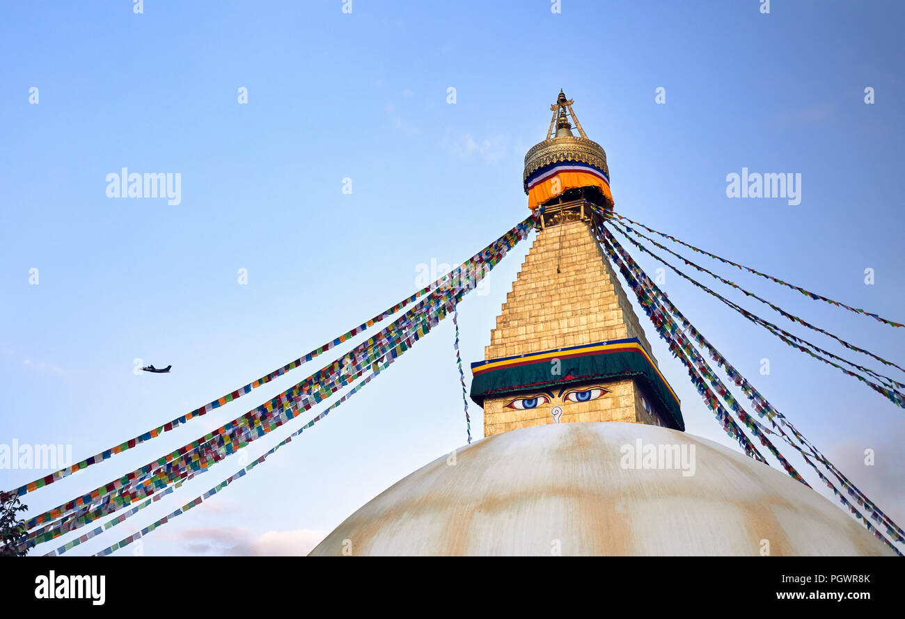 Bodnath Buddhist Stupa with prayer flags and airplane in Kathmandu - Stock Image
