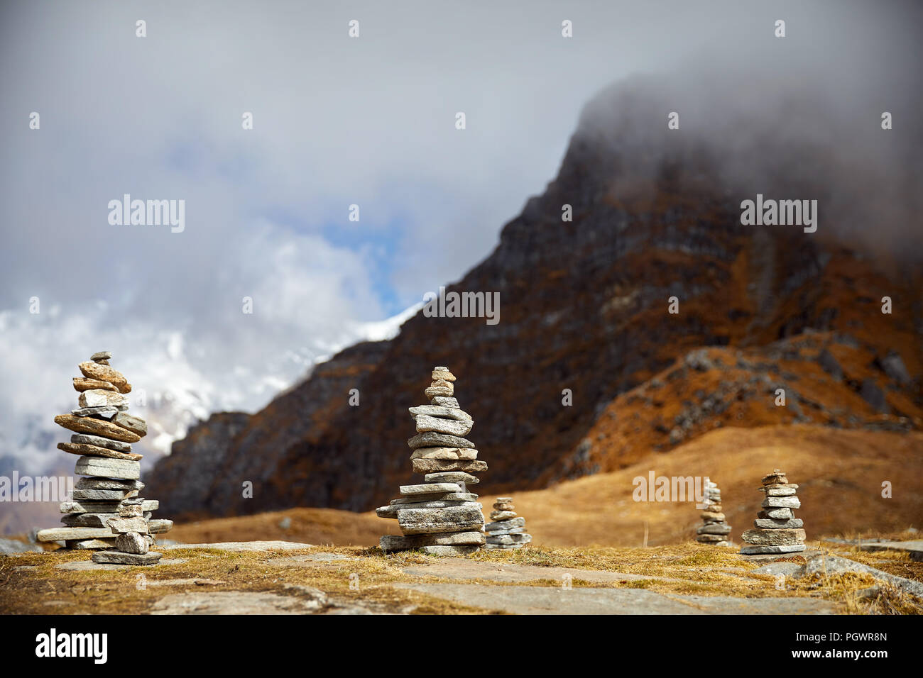 Small piles from stones on the Mardi Himal trek and cloudy peaks of Himalaya Mountains in Nepal - Stock Image