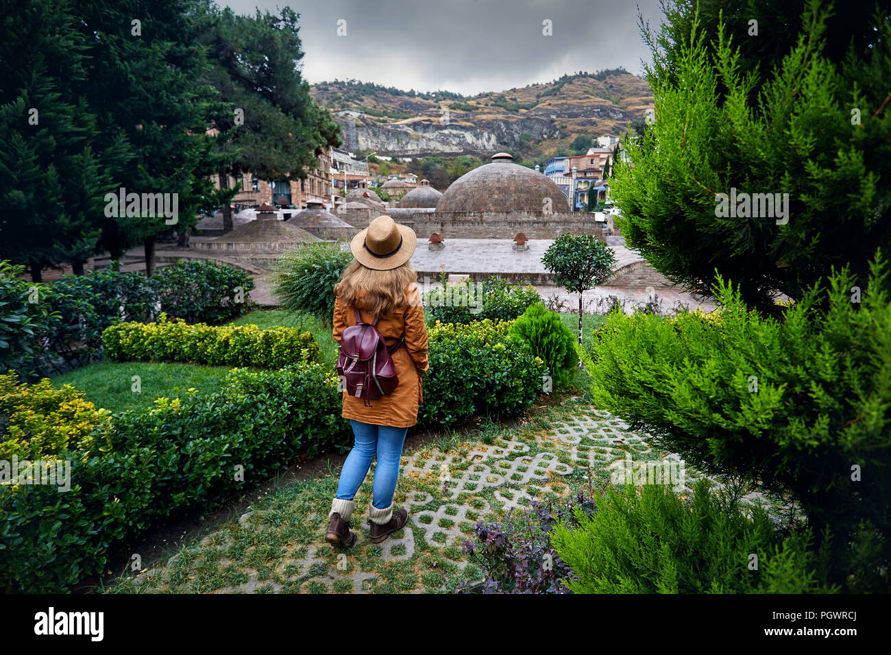 Beautiful woman in brown hat and jacket near the dome of Public Sulfuric bath district in central Tbilisi, Georgia - Stock Image