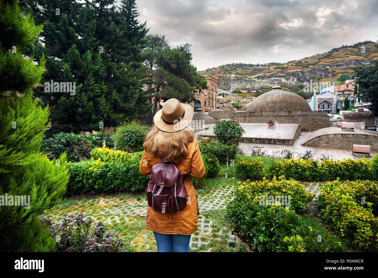Beautiful woman in brown hat and jacket going to the dome of Public Sulfuric bath district in central Tbilisi, Georgia - Stock Image