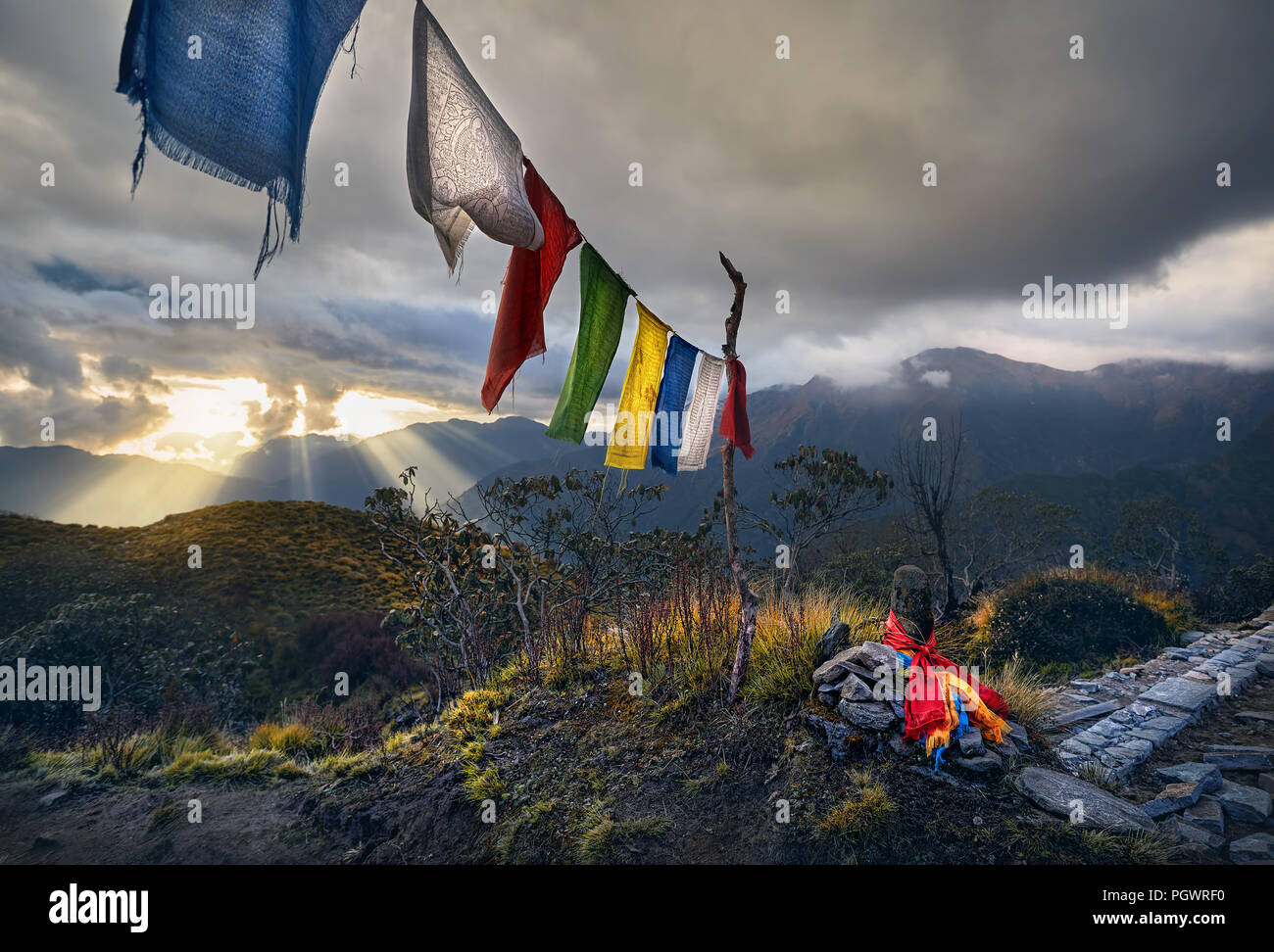 Small piles from stones and Tibetan prayer flags Lung Ta at the Mardi Himal Base Camp at cloudy sunset peaks of Himalaya Mountains in Nepal - Stock Image