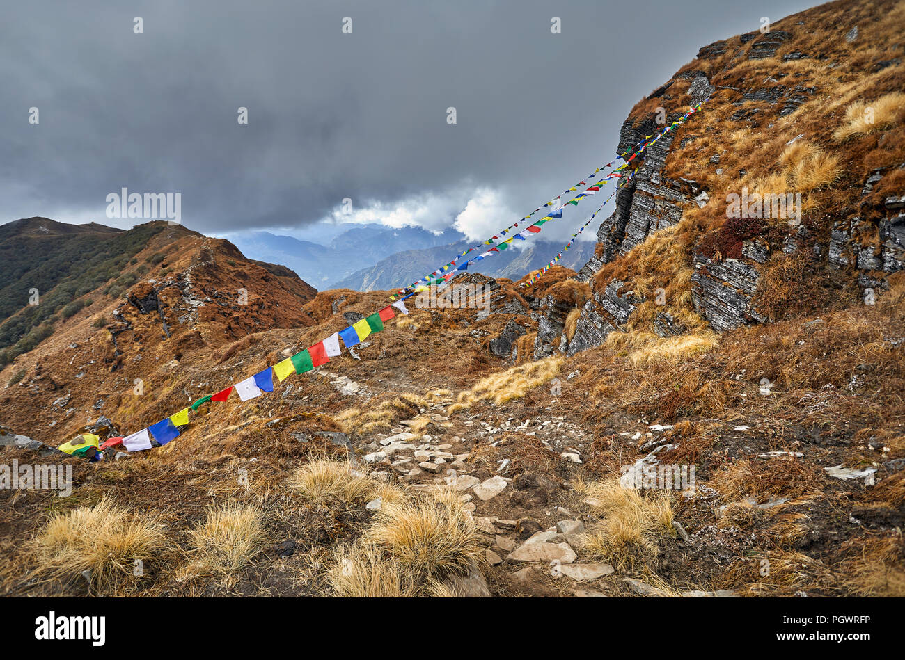 Small piles from stones and Tibetan prayer flags Lung Ta at the Mardi Himal Base Camp at cloudy peaks of Himalaya Mountains in Nepal - Stock Image