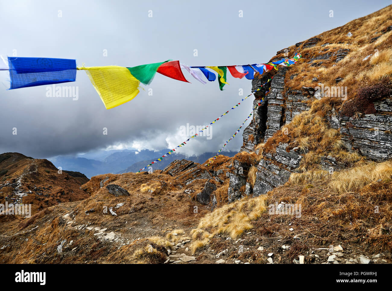 Rocks and Tibetan prayer flags Lung Ta at the Mardi Himal Base Camp at cloudy peaks of Himalaya Mountains in Nepal - Stock Image