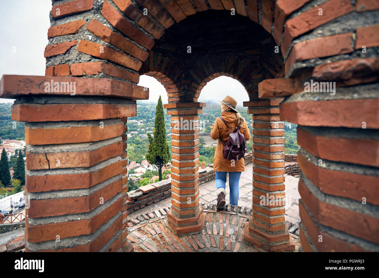Tourist woman in hat and backpack walking in the church at autumn foggy time in Signagi, Georgia - Stock Image