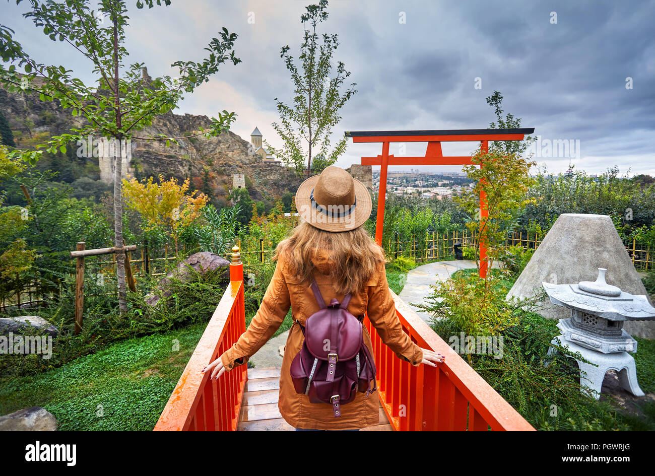 Woman in brown hat in Japanese garden and old castle Narikala at overcast cloudy sky in botanical garden of Tbilisi, Georgia - Stock Image