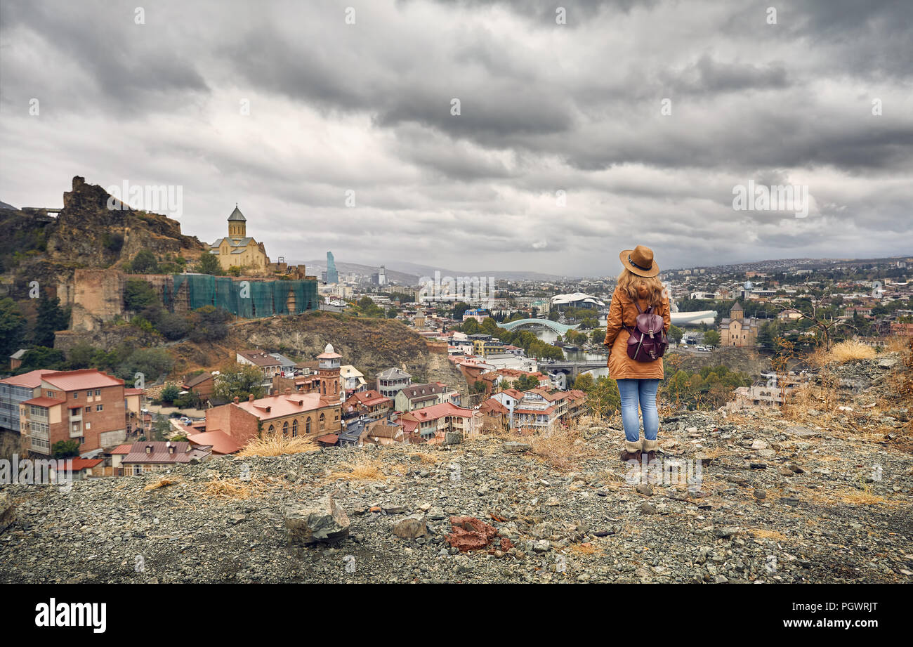 Woman in brown hat and backpack looking at Old medieval castle Narikala with overcast cloudy sky in Tbilisi, Georgia - Stock Image