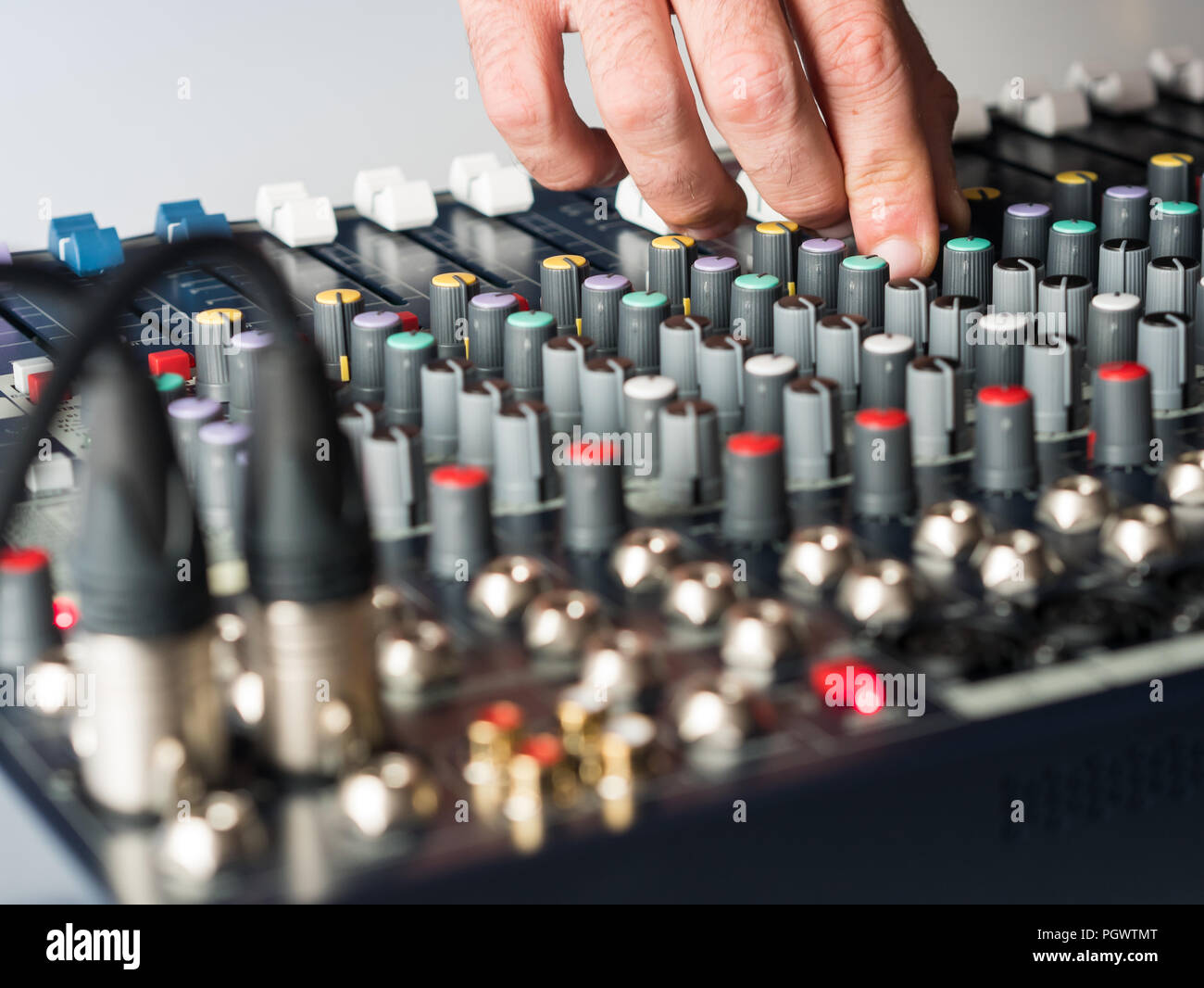 Dj adjusting buttons on audio mixer in studio close up Stock Photo