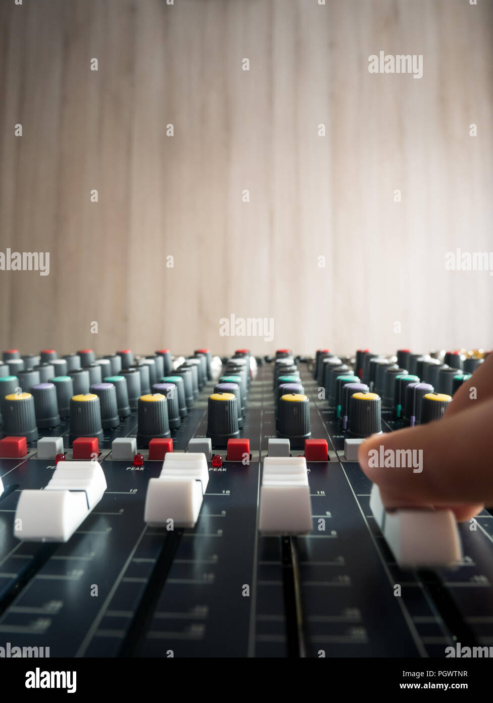Producing music in studio on audio mixer close up - Stock Image