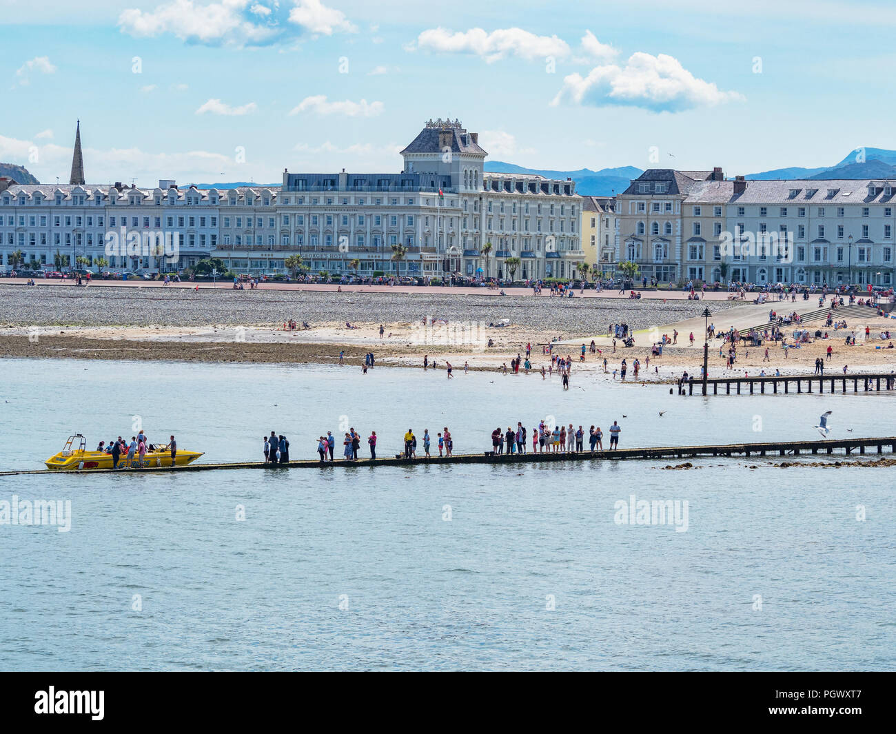 25 July 2018: Llandudno, Conwy, UK - A line of people queuing for boat trips on the boardwalk at Llandudno beach on a warm day during the July heatwav - Stock Image