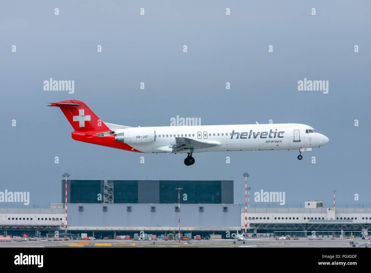 Helvetic Airways, Fokker F100 at Malpensa (MXP / LIMC), Milan, Italy - Stock Image