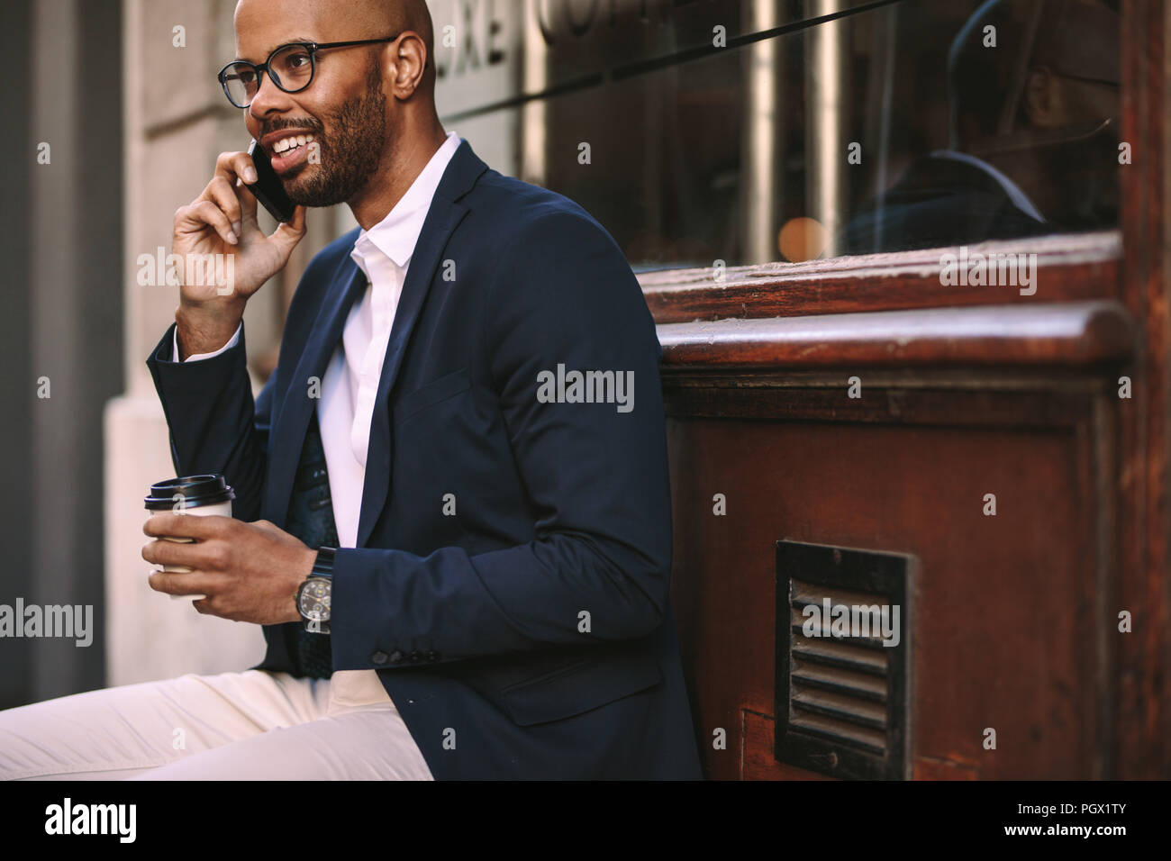 Happy african man relaxing outdoors with coffee and talking on mobile phone. Young man in business suit sitting outside and talking on the phone. Stock Photo