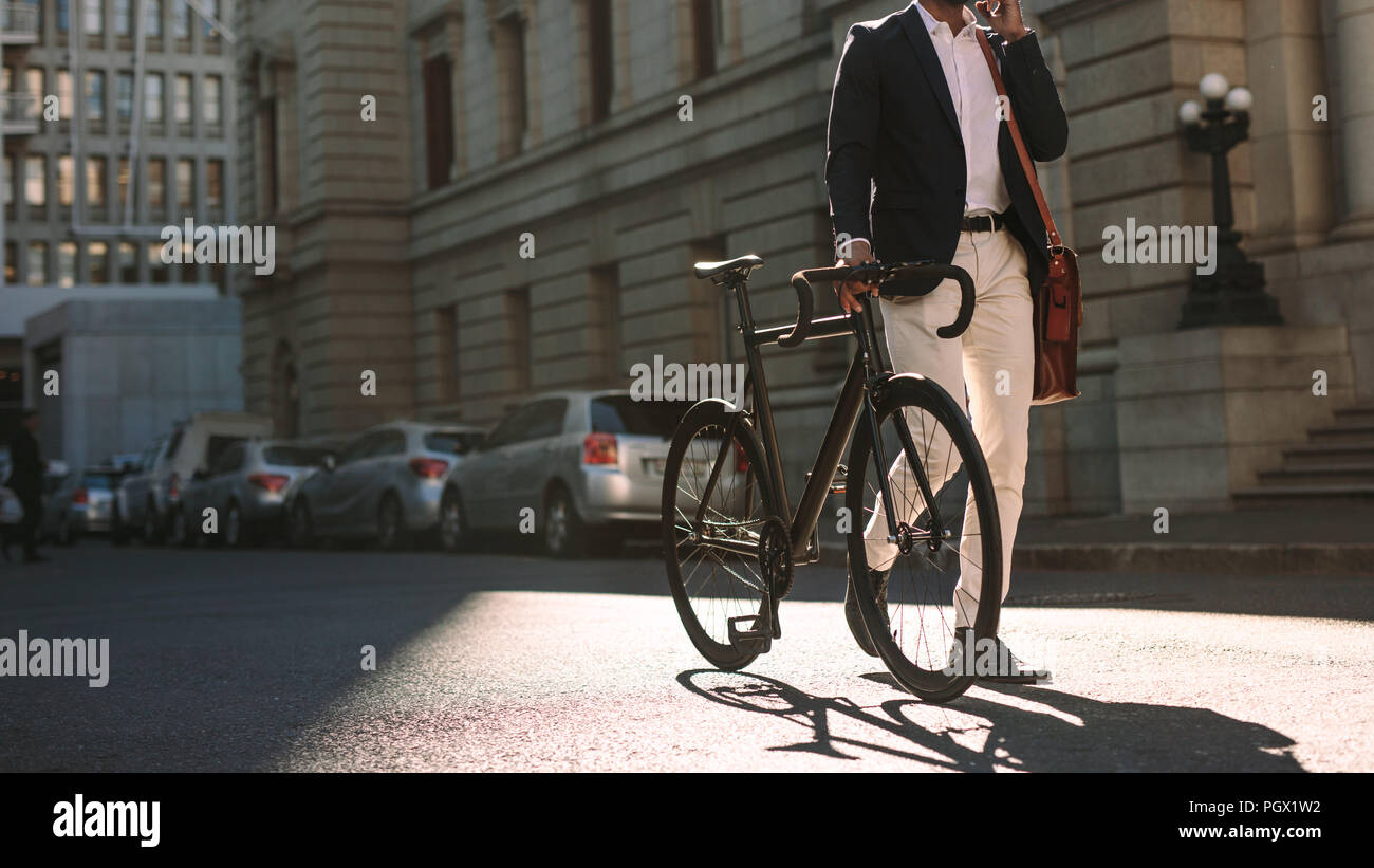 Cropped image of businessman walking on city street with a bicycle and talking on mobile phone. Man in formal wear going to work with cycle using phon - Stock Image