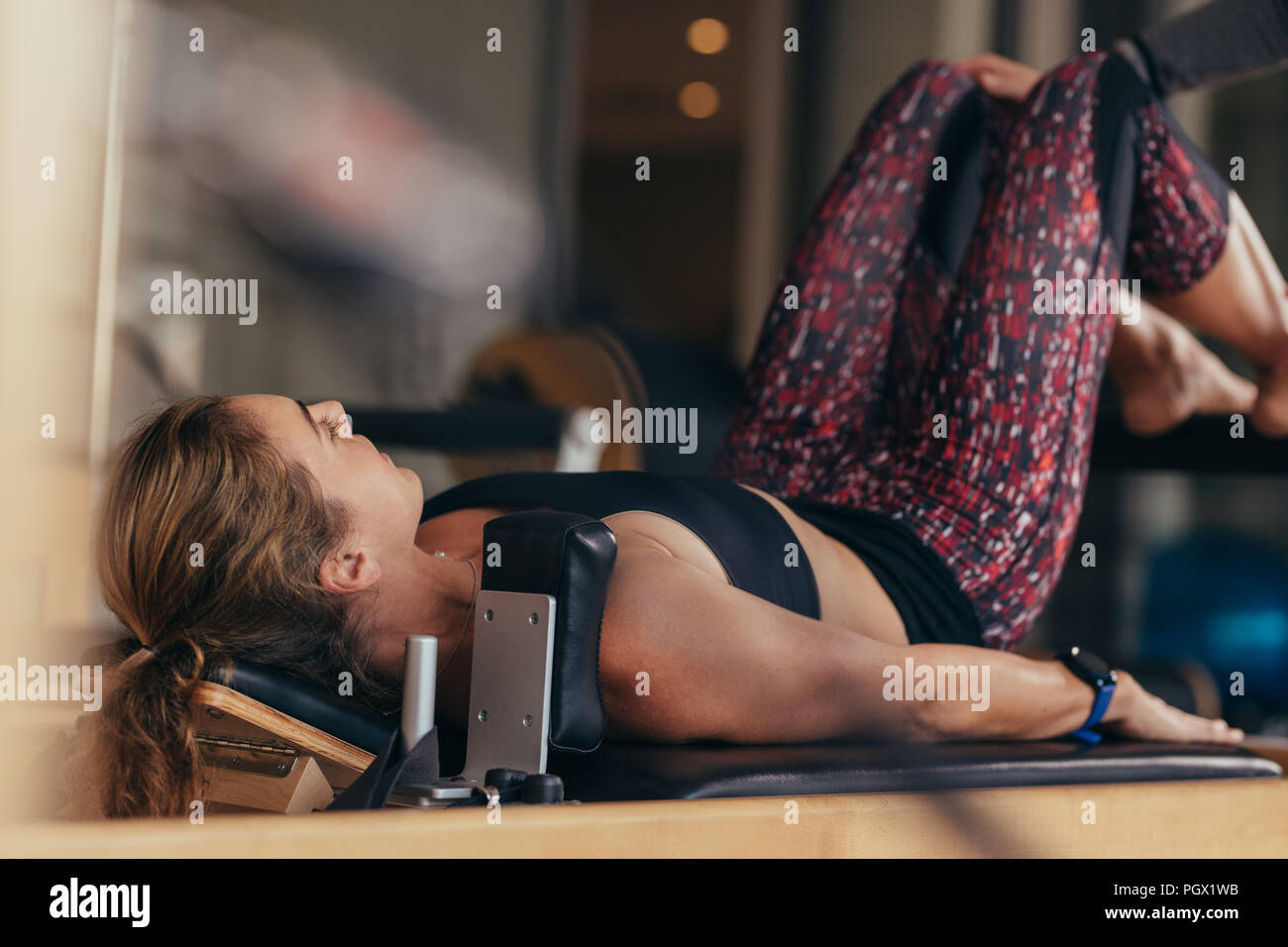 Fitness woman doing pilates workout lying on a fitness machine. Pilates woman at a gym doing exercises. - Stock Image