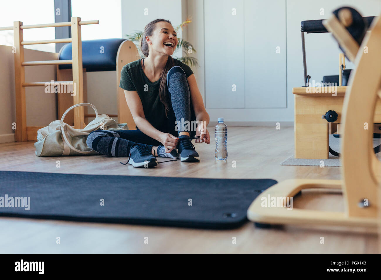 Smiling woman wearing her shoes after workout sitting at the gym. Woman sitting on floor at a pilates gym with her gym bag tying her shoelaces. - Stock Image