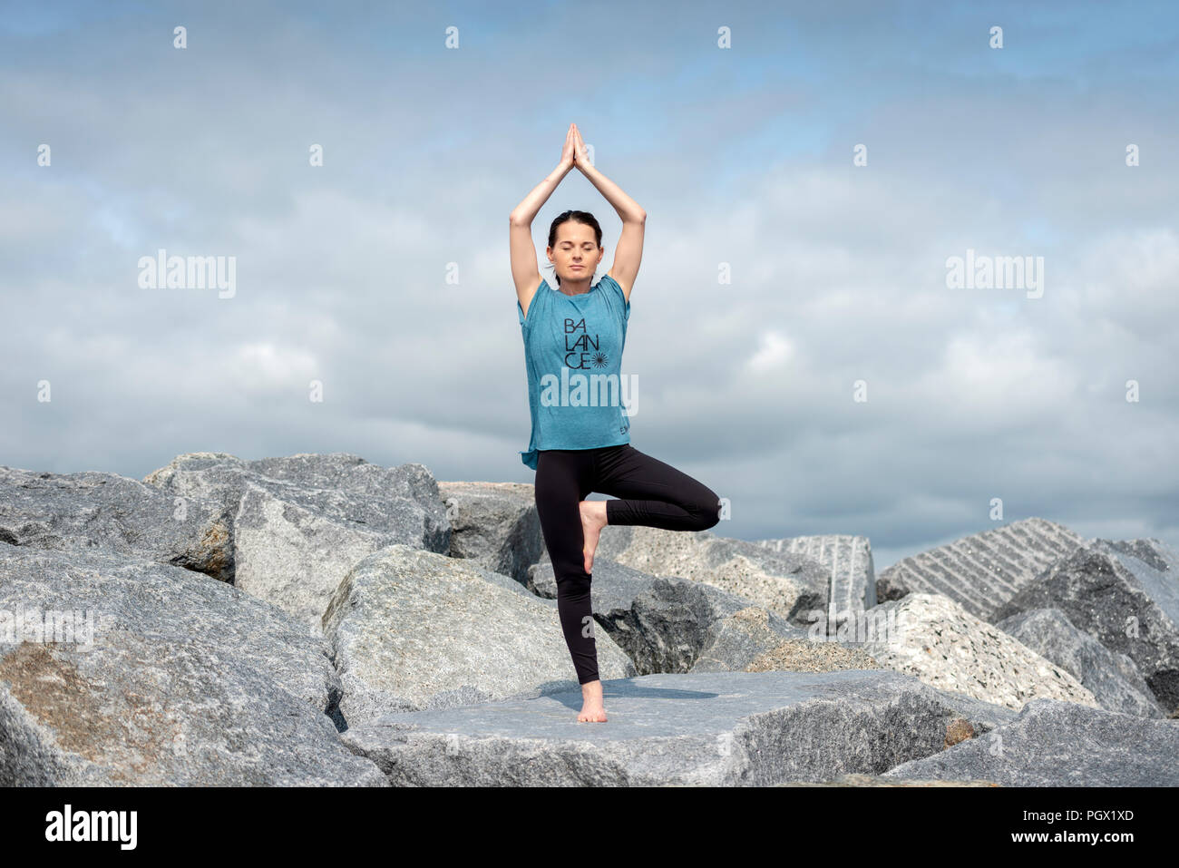 woman standing doing yoga, tree pose, wearing a tshirt with 'balance' slogan. - Stock Image
