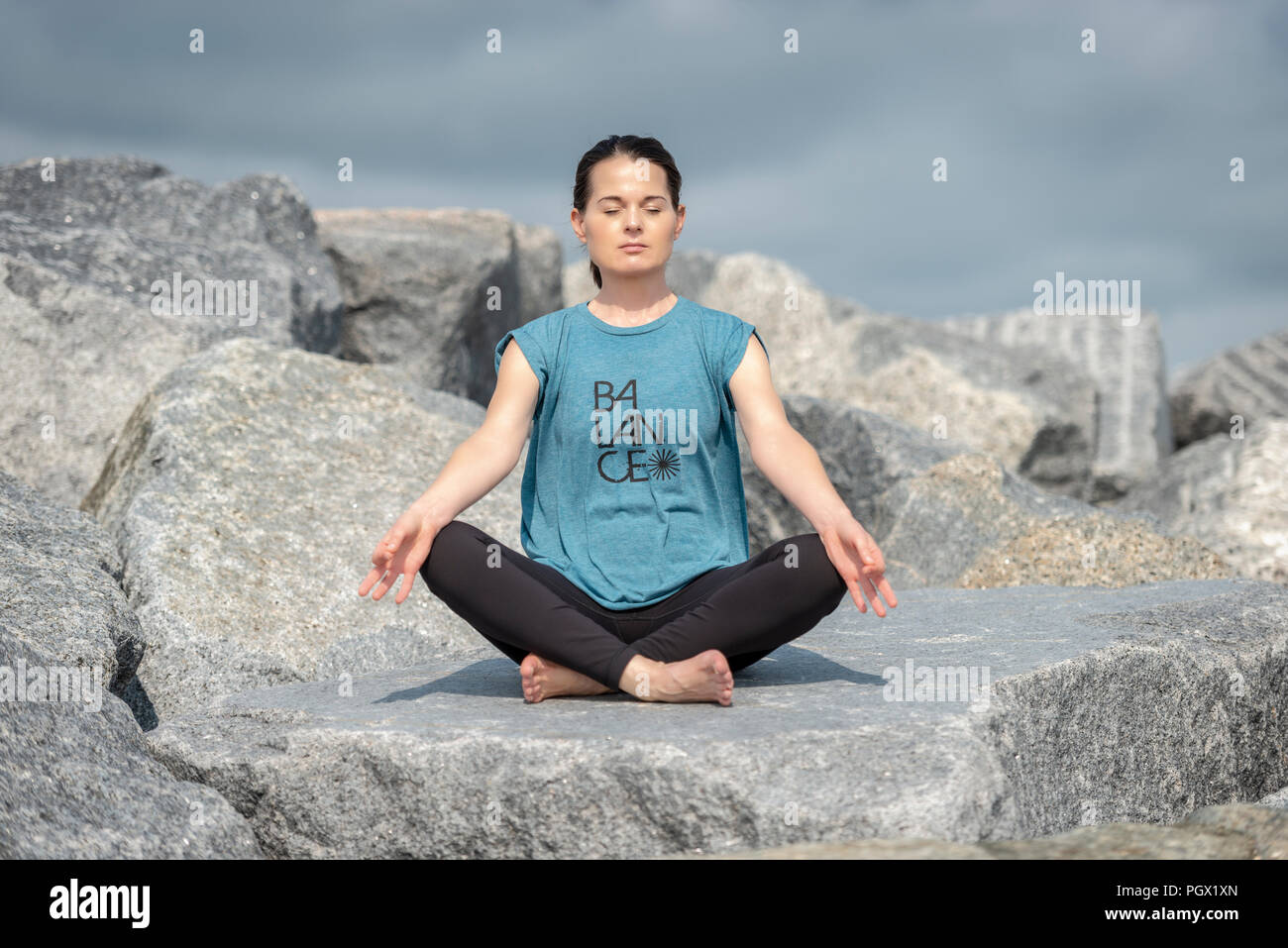 woman sitting meditating outside on rocks, wearing a tshirt with 'balance' slogan. - Stock Image