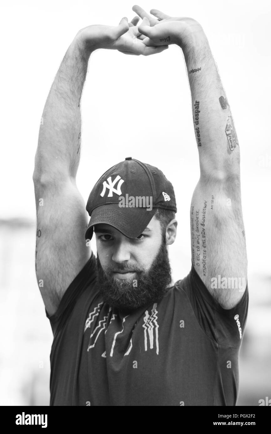 Portrait of a young hipster tattooed man with New York Yankees hat - Stock Image