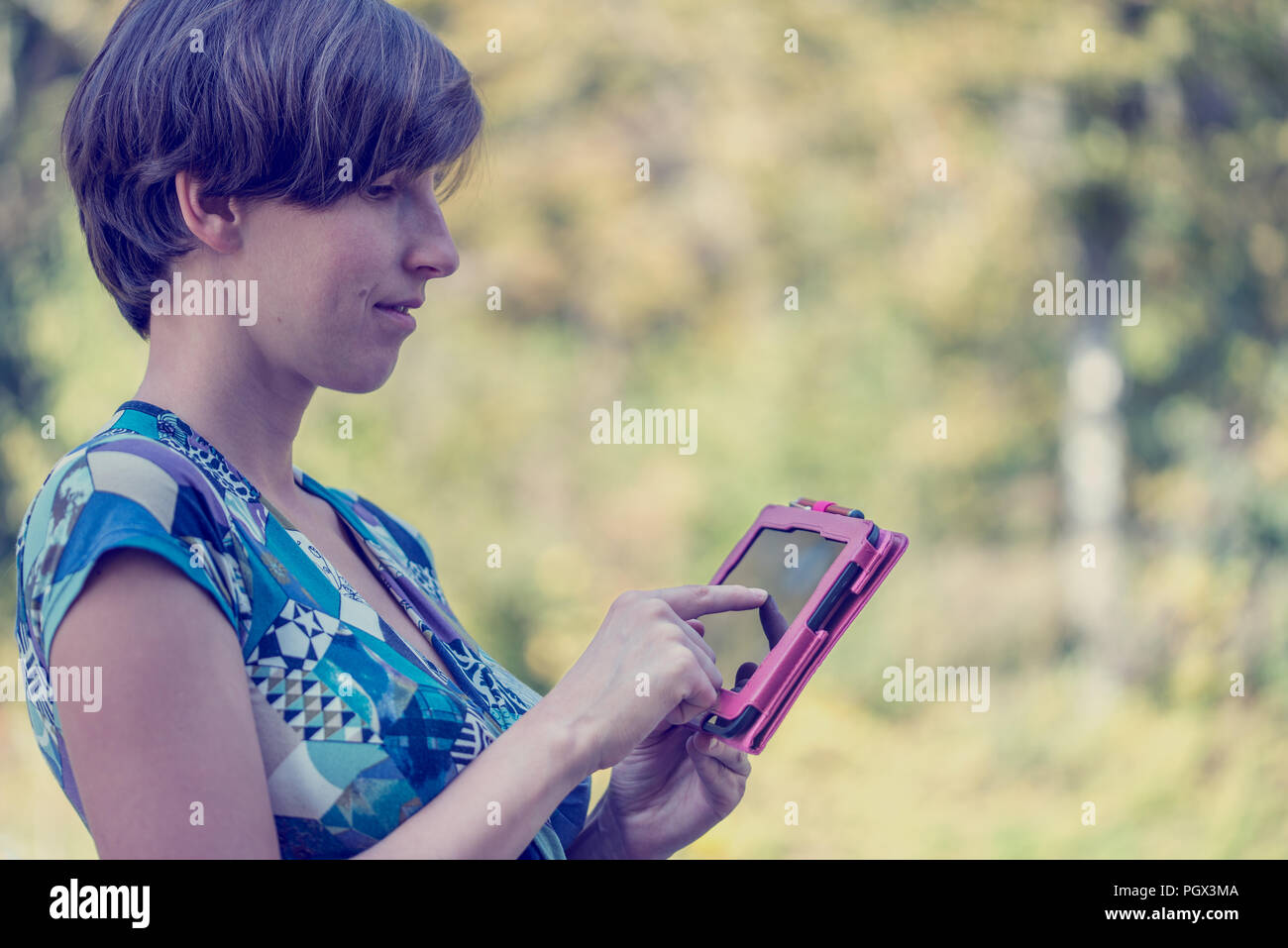 Attractive young woman standing in profile using a pink tablet outdoors navigating the touch screen with her finger against greenery with copyspace, v Stock Photo