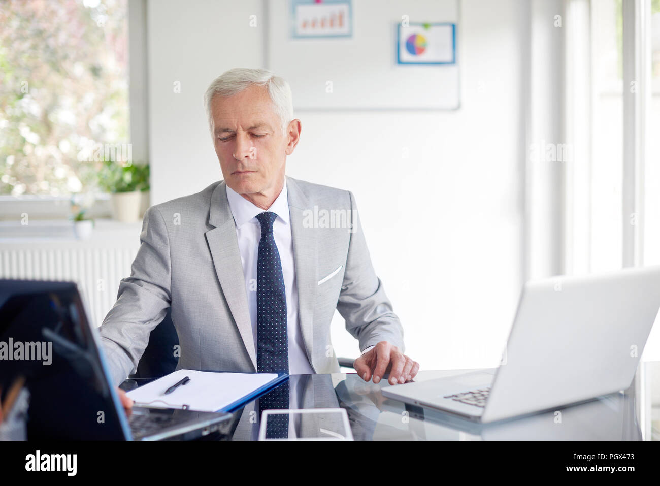 Shot of senior financial advisor businessman working on laptop while sitting at office. Stock Photo