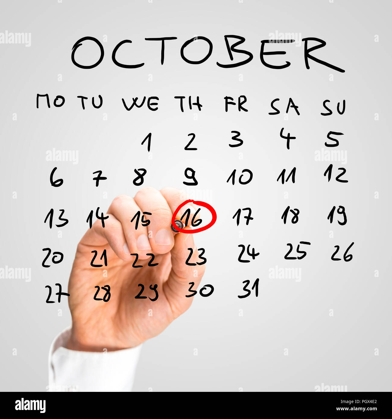 Man ringing the 16th of November on a handwritten calendar for October in red with a marker as a reminder that it is World Food Day and an important e - Stock Image