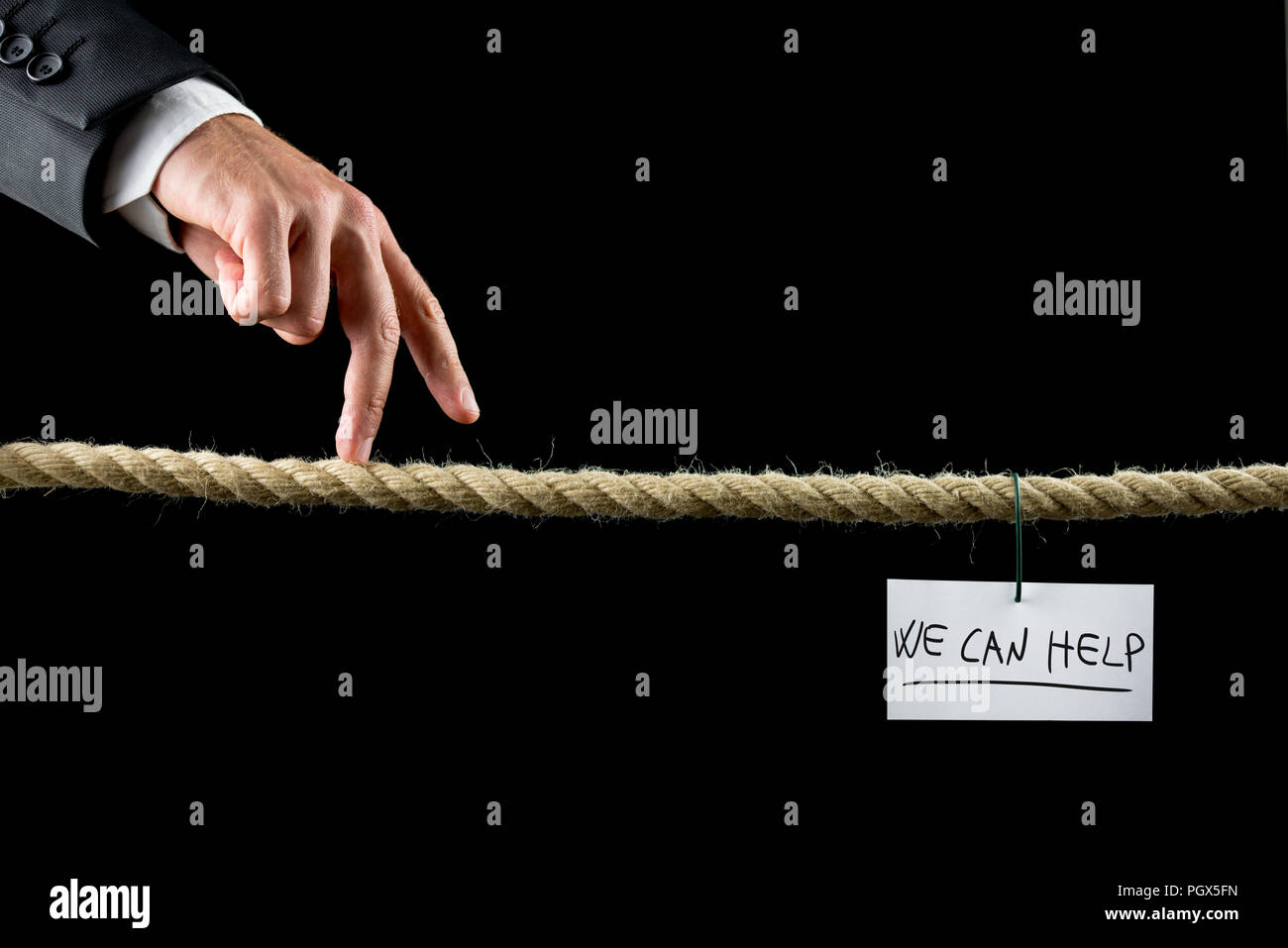 We Can Help concept with a hand written note bearing the words hanging on a wire from a rope suspended over a black background with a businessman walk - Stock Image
