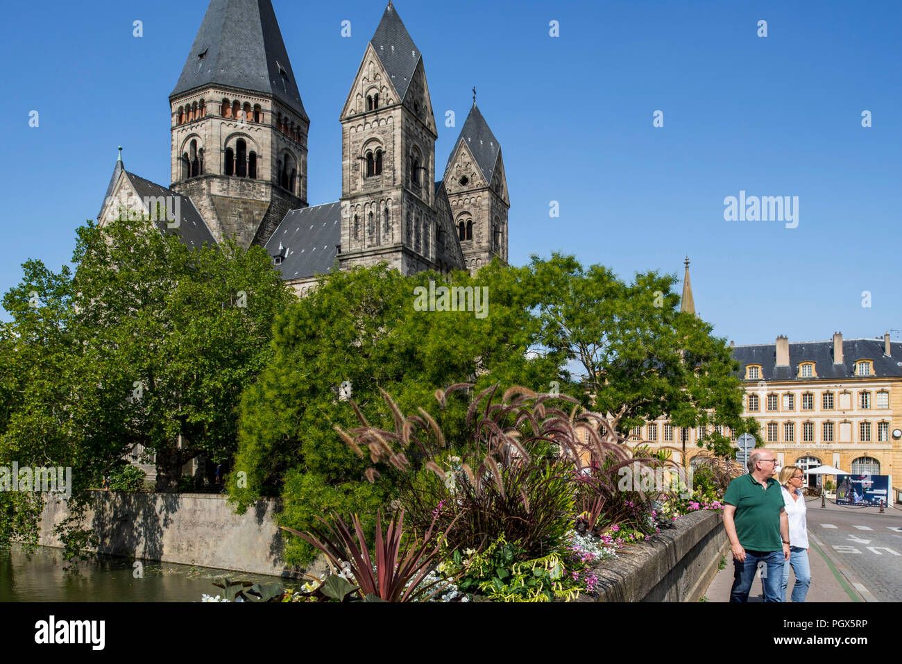 Temple neuf / Nouveau Temple Protestant church and tourists on the Pont des Roches over the Moselle river in the city Metz, Moselle, Lorraine, France Stock Photo