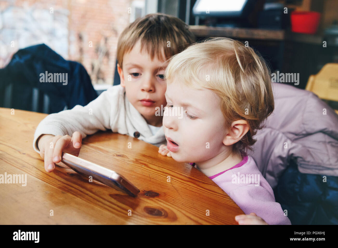 Portrait of two children toddlers boy and girl playing cell phone tablet games, watching cartoons movie, sitting at table in restaurant, real lifestyl - Stock Image