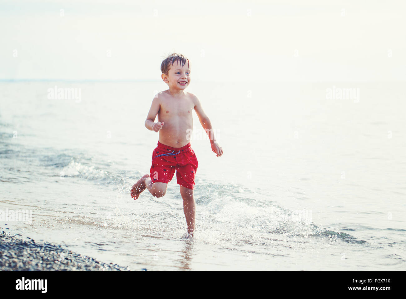 Portrait of funny adorable white Caucasian one young little boy in red swim shorts running on beach by water ocean sea, emotional healthy active lifes - Stock Image