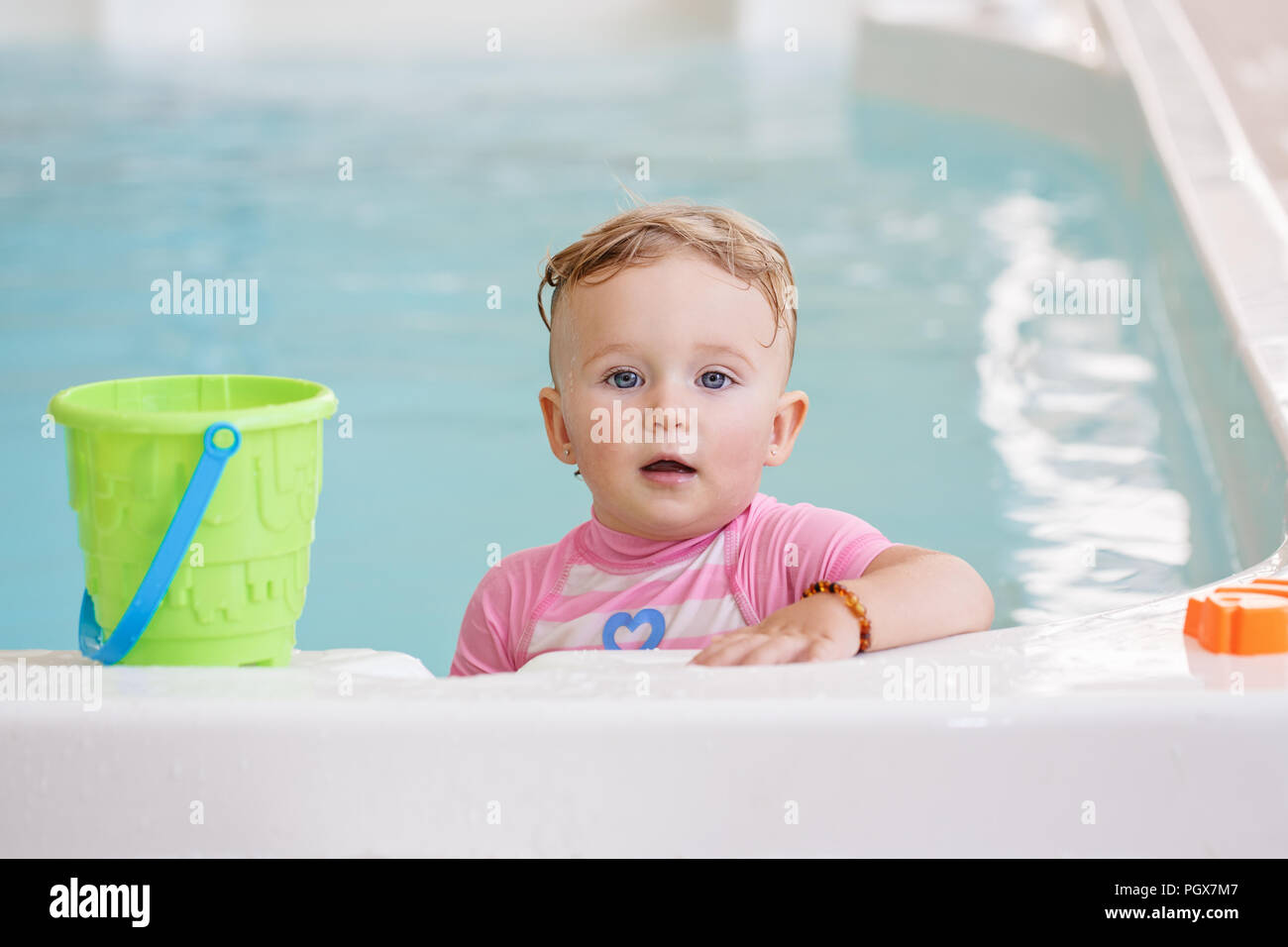 Portrait of white Caucasian baby girl playing with toys in water standing by swimming pool nosing inside, looking in camera, training to swim, healthy Stock Photo