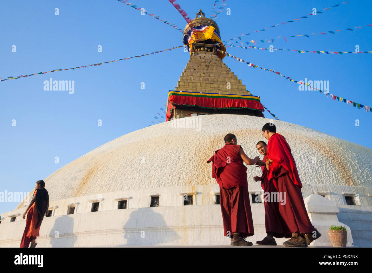 Bodhnath , Kathmandu, Bagmati, Nepal : Buddhist monks in maroon robes walk around the Great stupa of Bodhnath, the largest in Asia and one of the larg - Stock Image