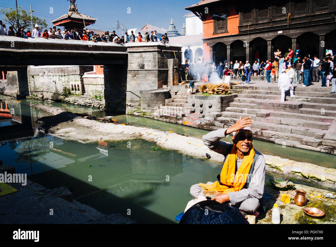 Pashupatinath Temple, Kathmandu Valley, Bagmati, Nepal, South Asia : A brahman sits by the Bagmati river where cremations are taking place at  Pashupa - Stock Image