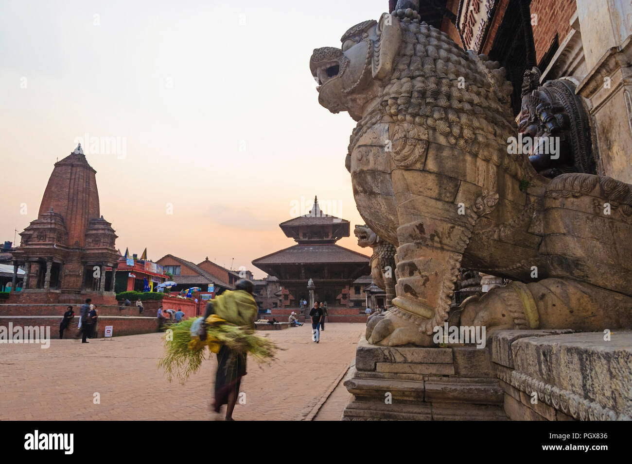 Bhaktapur, Kathmandu Valley, Bagmati, Nepal : A man walks past the lion statues outside the Royal palace at sunset in Durbar square at the Unesco Worl - Stock Image