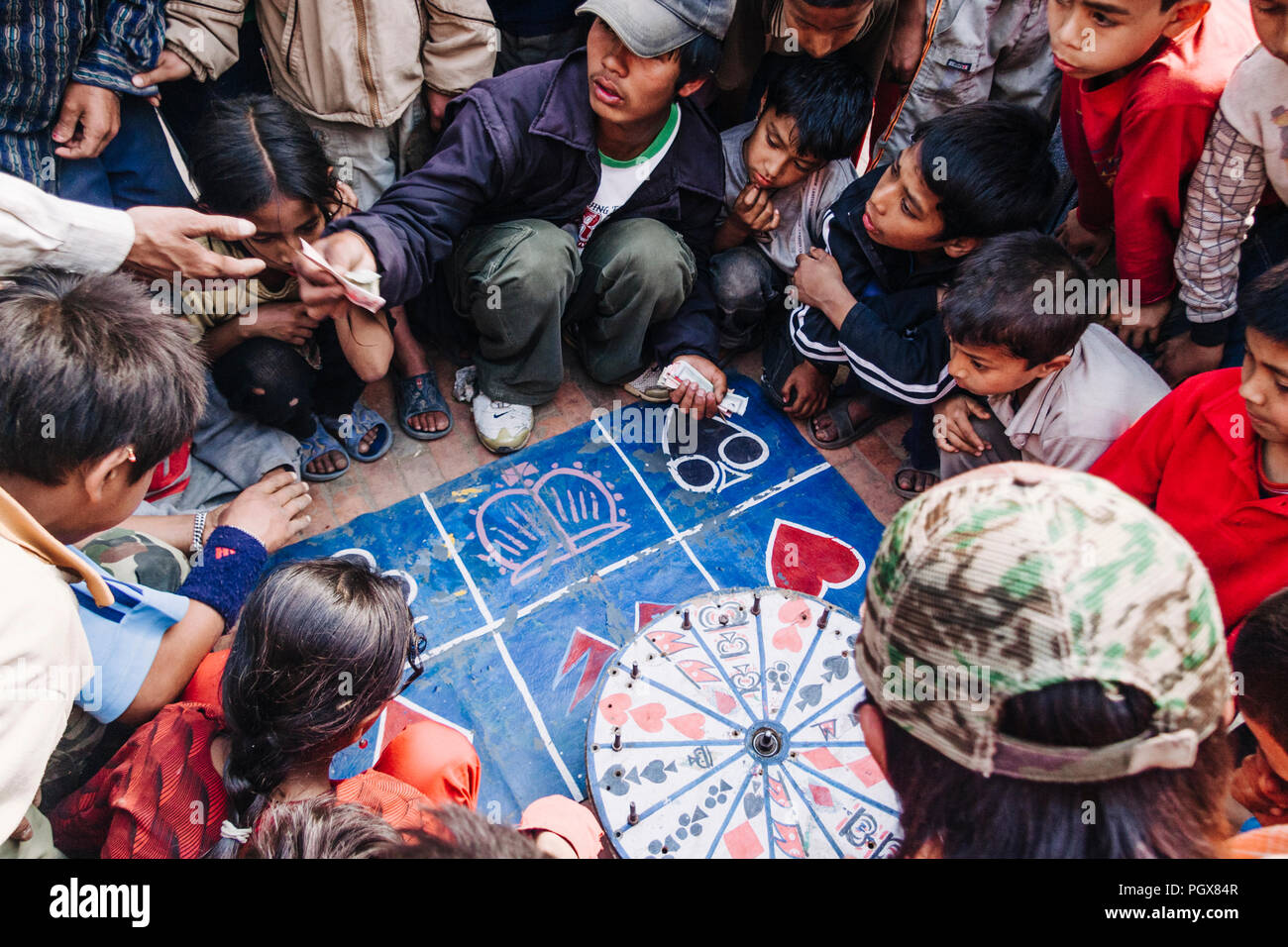 Bhaktapur, Kathmandu Valley, Bagmati, Nepal :  A young men surrounded by children squats by a roulette betting stall at Taumadhi Tole square before th - Stock Image