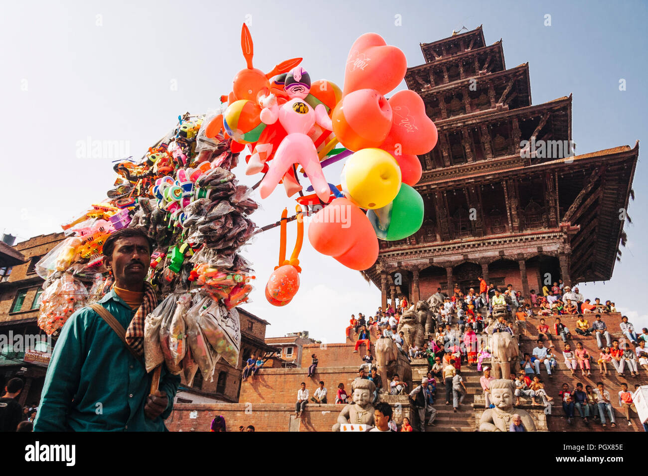 Bhaktapur, Kathmandu Valley, Bagmati, Nepal : A balloons vendor stands as a crowd of onlookers gathers at the steps of the Nyatapola temple at Taumadh - Stock Image