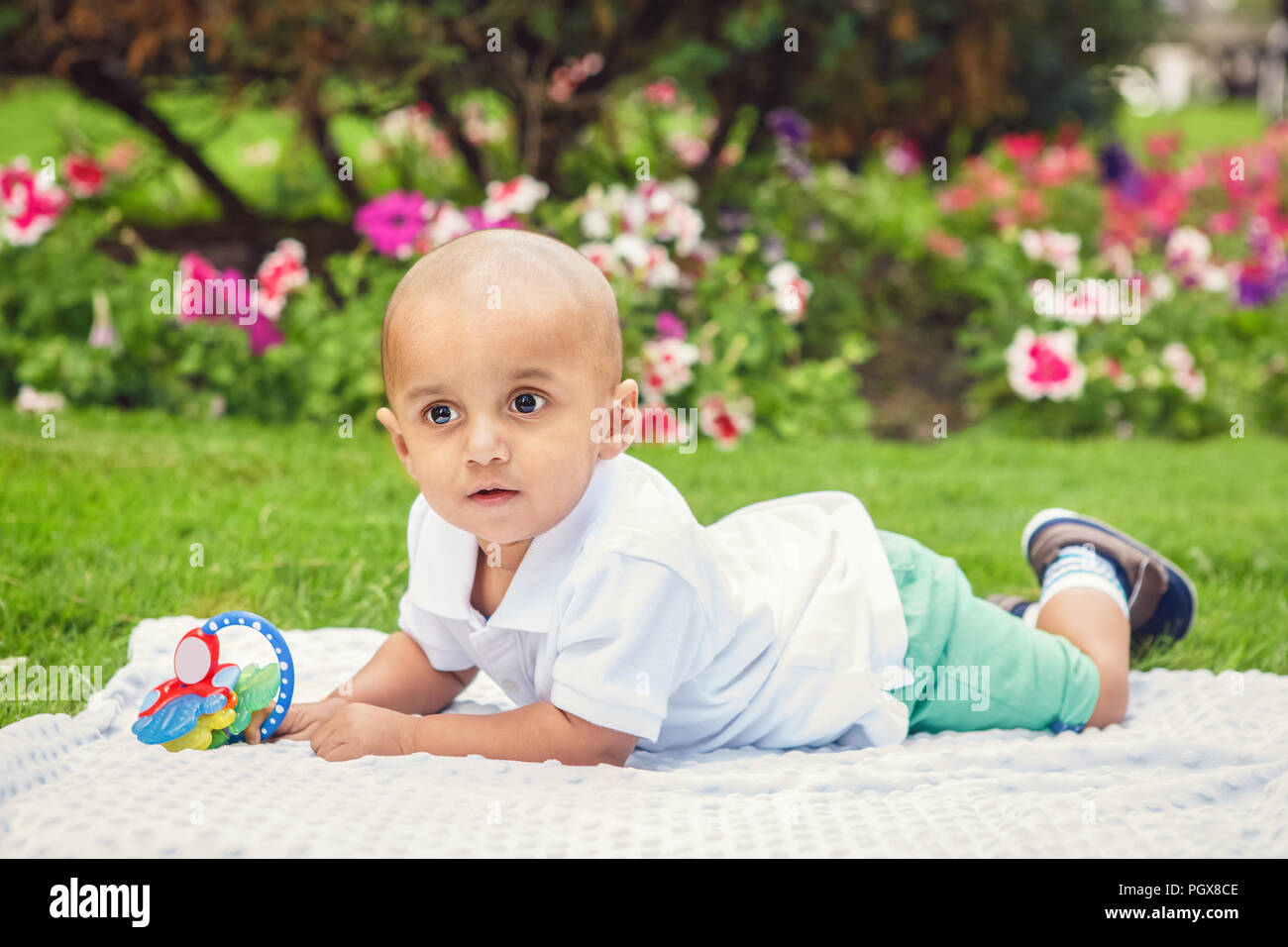 Portrait of cute adorable little indian South Asian or Middle Eastern infant boy in white shirt laying on ground with toys in park outside on bright s Stock Photo