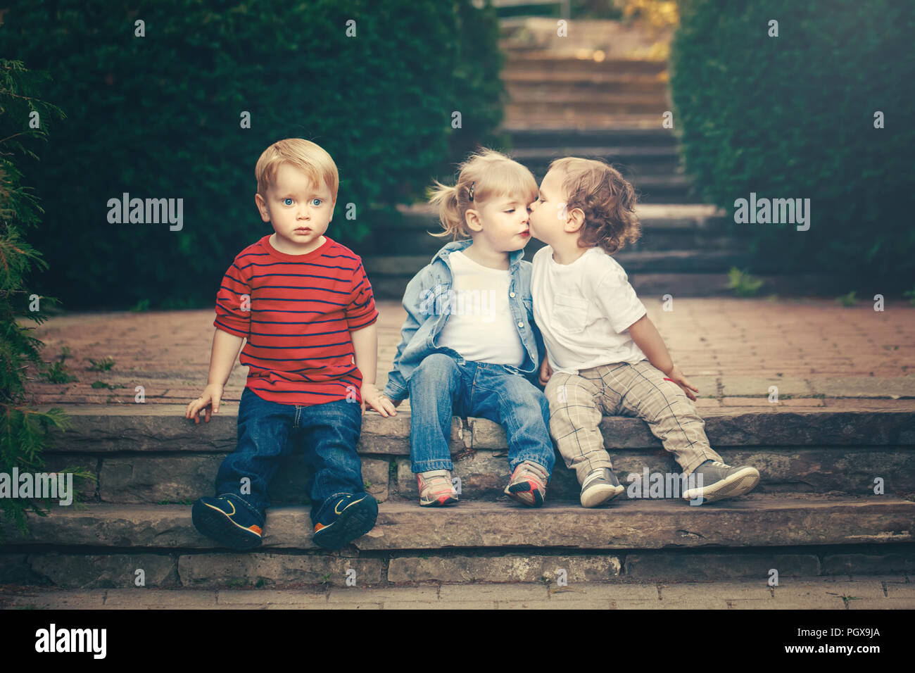 Group of three cute funny adorable white Caucasian children toddlers boys girl sitting together kissing each other. Love jealousy friendship childhood - Stock Image