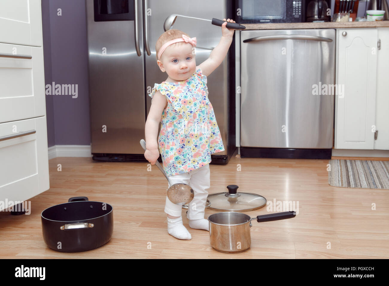 Portrait of cute adorable funny little Caucasian blonde baby girl playing in kitchen with utensils, pot and ladle, child with funny face emotional exp - Stock Image